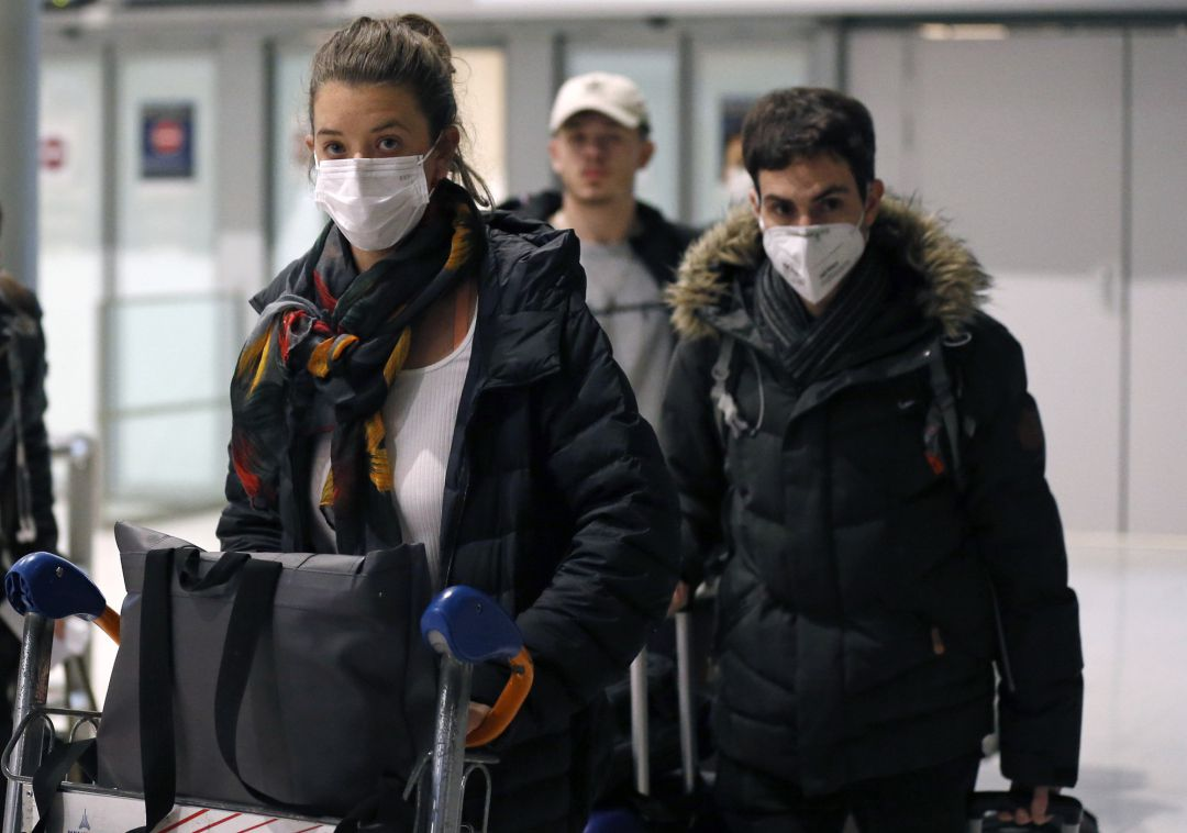 PARIS, FRANCE - FEBRUARY 10: Passengers coming from China wearing protective masks leave the terminal after landing in Charles De Gaulle Airport on February