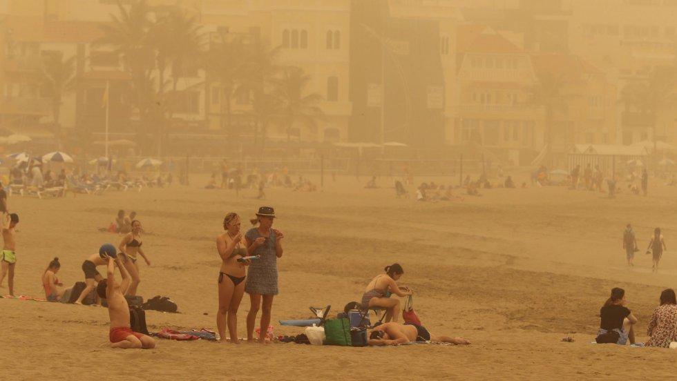 Canarias está afectada desde este sábado por una intensa calima (arena y polvo del desierto del Sáhara en suspensión) provocada por viento fuerte con rachas muy fuertes de componente este, que se intensificará el domingo, y puede superar los 80-100 km por hora, sobre todo en zonas altas y de medianías donde no se descarta que superen los 120 km/h. En la imagen, varias personas en la playa de Las Canteras de Las Palmas de Gran Canaria.