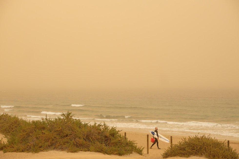 Un surfero se dispone a coger olas en Playa Blanca a pesar de la calima. Canarias está afectada desde este sábado por una intensa calima (arena y polvo del desierto del Sáhara en suspensión) provocada por viento fuerte con rachas muy fuertes de componente este, que se intensificará el domingo, y puede superar los 80-100 km por hora, sobre todo en zonas altas y de medianías donde no se descarta que superen los 120 km/h.