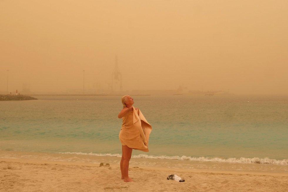 Una turista toma un baño en Playa Chica en Puerto del Rosario. Canarias está afectada desde este sábado por una intensa calima (arena y polvo del desierto del Sáhara en suspensión) provocada por viento fuerte con rachas muy fuertes de componente este, que se intensificará el domingo, y puede superar los 80-100 km por hora, sobre todo en zonas altas y de medianías donde no se descarta que superen los 120 km/h