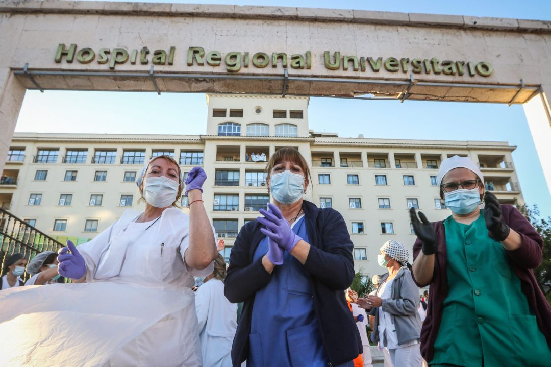 03 April 2020, Spain, Malaga: Medical staff working on the coronavirus outbreak at the Malaga Regional Hospital, applaud as they are cheered on during the daily tribute to health care workers
