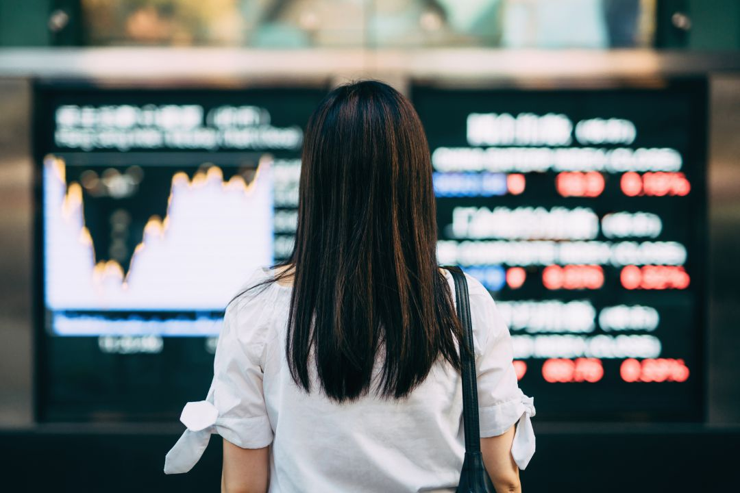 Businesswoman looking at stock exchange market display
