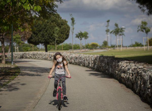 Una niña con mascarilla monta en bicicleta por el parque en el tercer día de desconfinamiento de niños y preadolescentes durante el estado de alarma por la crisis del coronavirus en el que los menores de 14 años pueden salir durante una hora, de 09:00 a 21:00 junto a un máximo de otros dos menores y un adulto que viva con ellos. En Sevilla (Andalucía, España), a 28 de abril de 2020  28 ABRIL 2020  María José López / Europa Press  28/04/2020