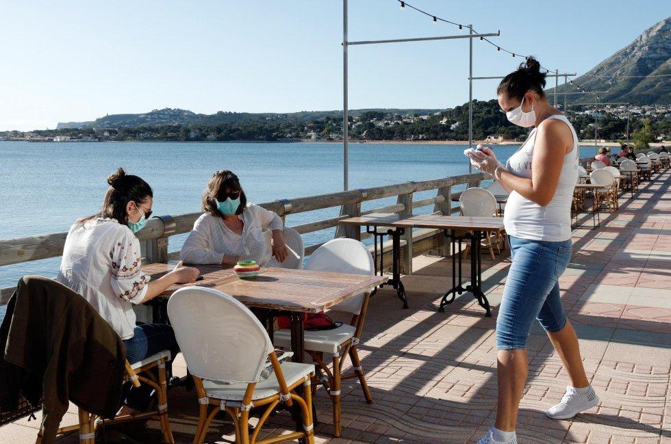 Una camarera atiende a dos clientas en una terraza en la localidad Alicantina de Denia, uno de los territorios de España que comienza la Fase 1.