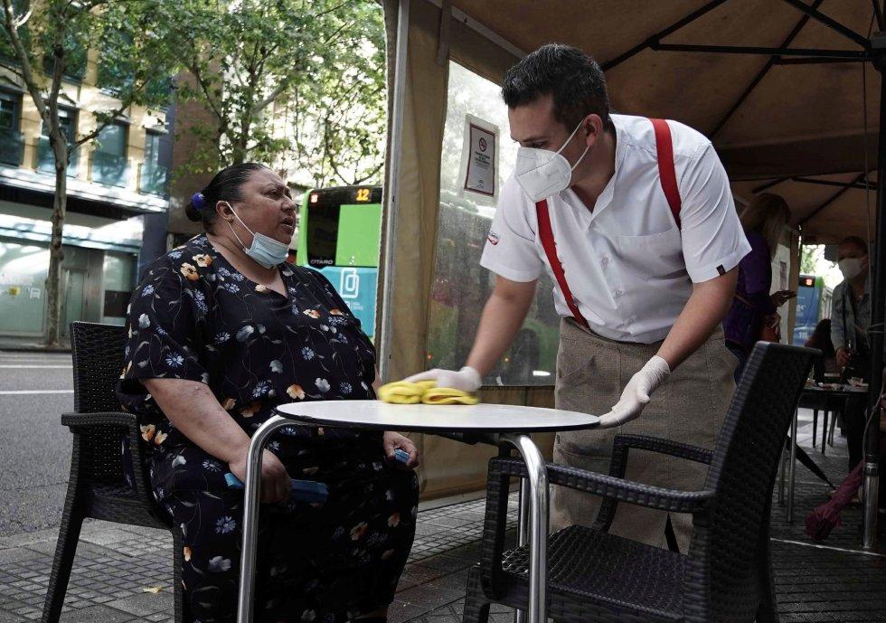 Un camarero atiende a una señora en la terraza de un bar en el centro de Córdoba, este lunes, cuando comienza la fase 1 de la desescalada en la provincia.