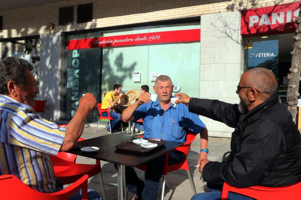 Tres clientes de la cafetería Panishop de Tarragona brindan simbólicamente con las tazas de cafè en el primer día de la fase 1.