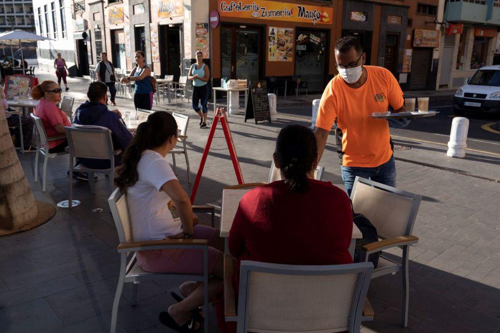 Un camarero atiende a los clientes en la terraza de un bar de Puerto de la Cruz (Tenerife).