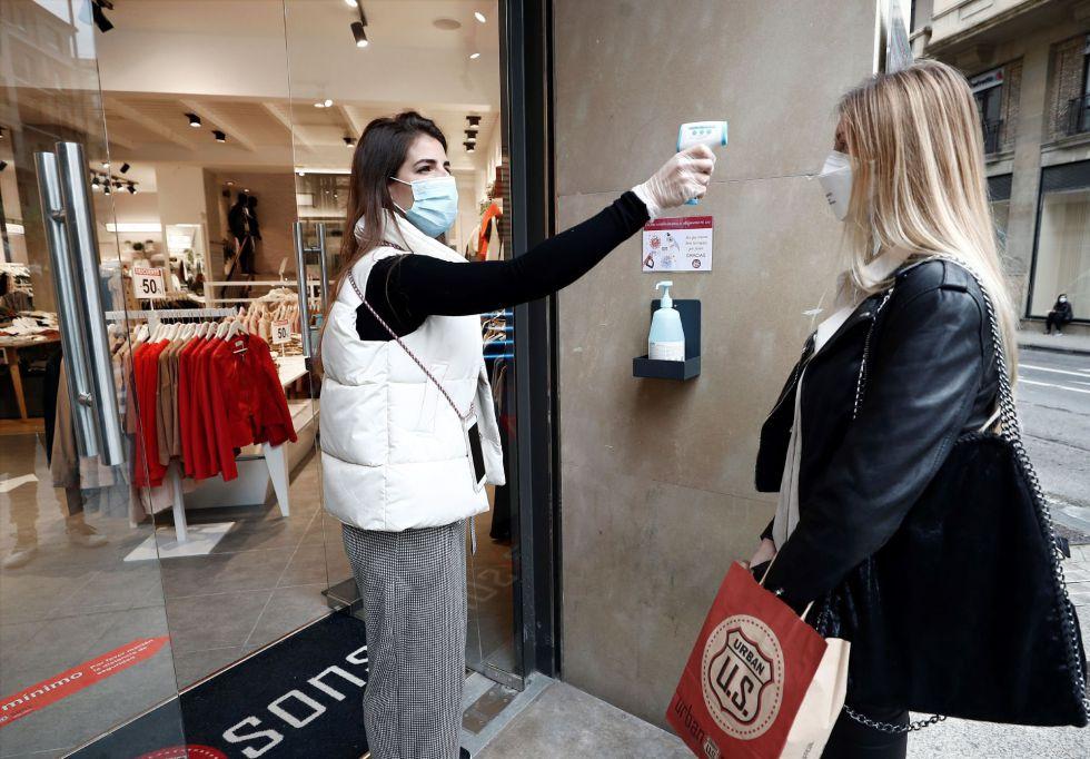 La encargada de la tienda Urban U.S situada en una de las arterias comerciales mas importantes dePamplona toma la temperatura a uno de los trabajadores antes de entrar a la tienda y proceder a su apertura al público.