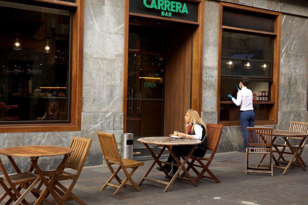Una mujer desayuna en una terraza de un bar de La Laguna, en Tenerife, donde este lunes comenzó la Fase 1 de la desescalada y por ello está autorizado la apertura del pequeño comercio con restricción de aforo.