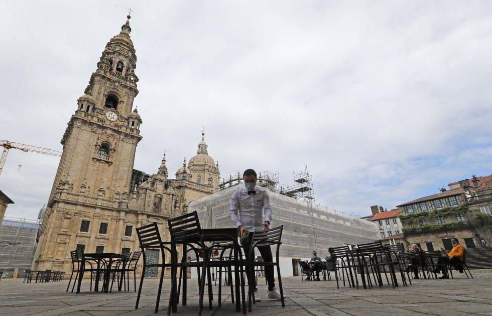 Un camarero monta la terraza de la plaza de A Quintana, ante la catedral, en el primer día de la fase 1 de la desescalada del confinamiento por el Civid 19, esta mañana en Santiago de Compostela.