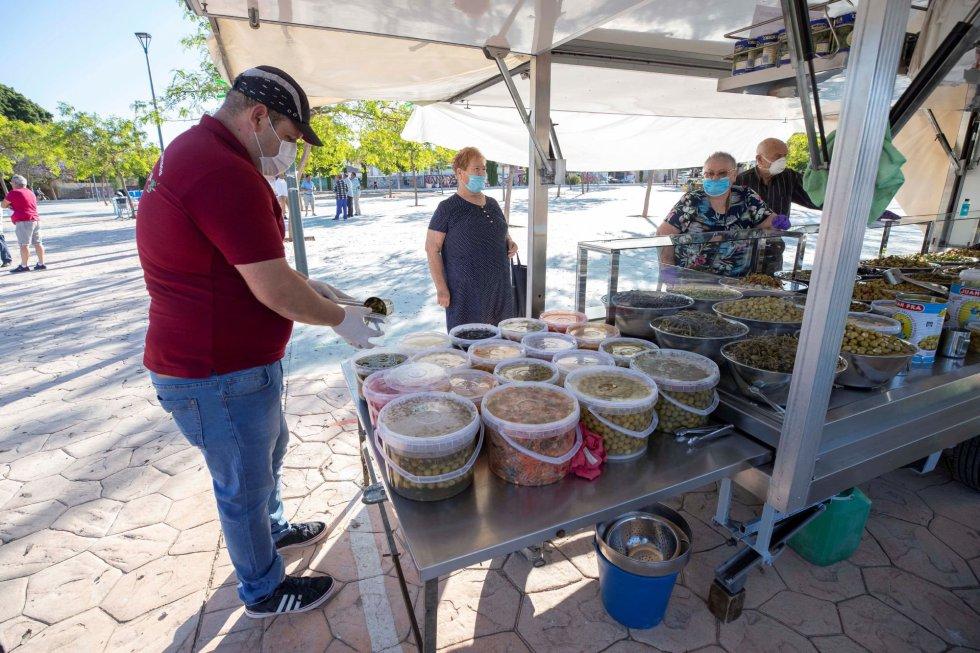 Varias personas compran en un puesto de encurtidos del mercadillo semanal del Barrio Peral de Cartagena, este lunes, primer día de la fase 1 de desescalamiento por la pandemia.