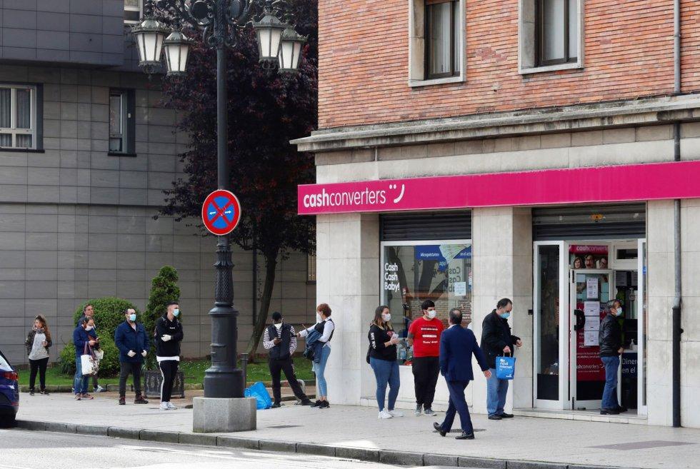 Varios ciudadanos hacen cola ante una tienda de compra-venta de artículos de segunda mano, este lunes, en Oviedo.