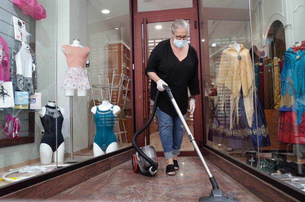 Una mujer pasa el aspirador a la entrada de una tienda de ropa abierta al público en Zaragoza.