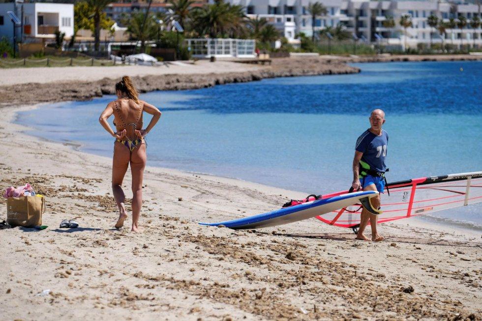 Varias personas disfrutan del sol en la playa de Talamanca en Ibiza.