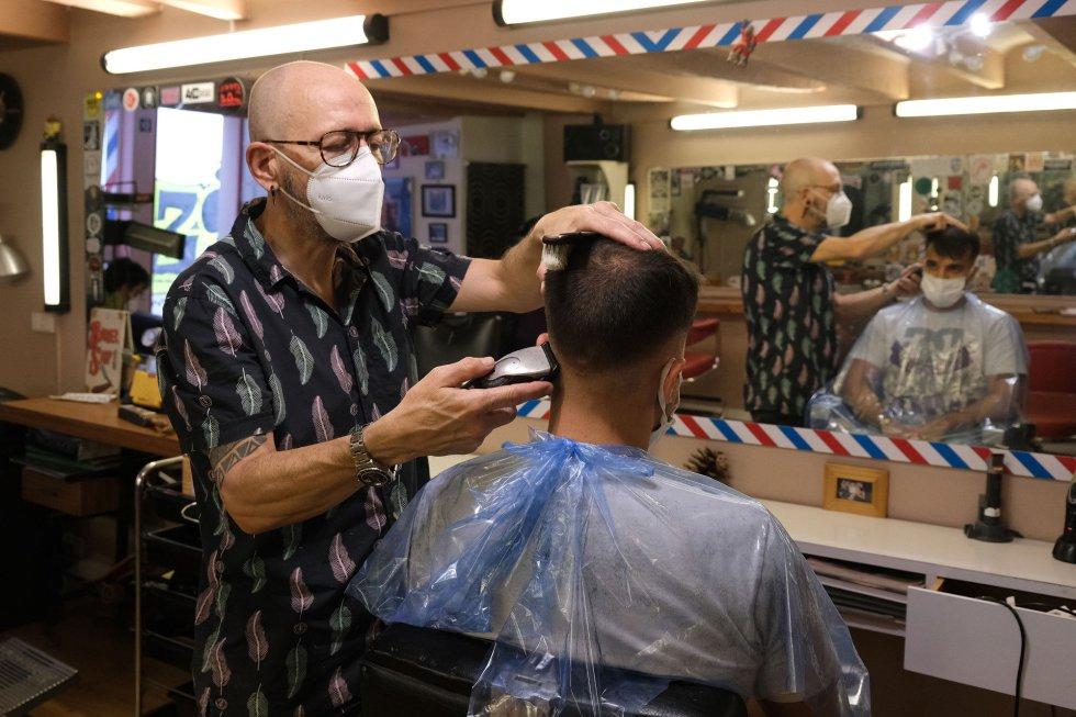 Un peluquero pasa la maquinilla de afeitar a un cliente en Palma de Mallorca el día en que el que la isla, junto con Menorca e Ibiza, inicia este lunes, 11 de mayo.