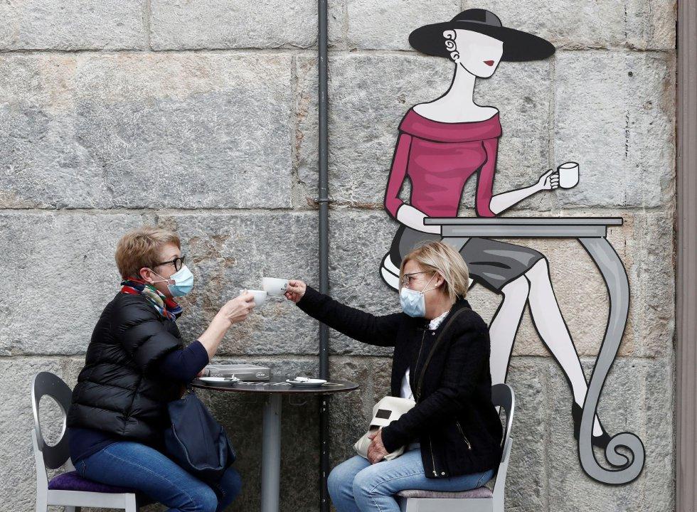 """Dos amigas """"brindan"""" con su primer café sentadas en la terraza de la Plaza del Consejo de Pamplona después de mas de 50 días de confinamiento en el que estos negocios han permanecido cerrados por el COVID-19."""