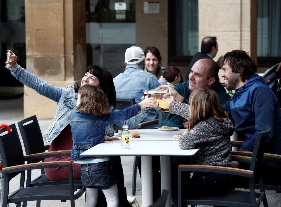 Una familia sentada en la terraza de la Plaza del Castillo de Pamplona después de mas de 50 días de confinamiento.