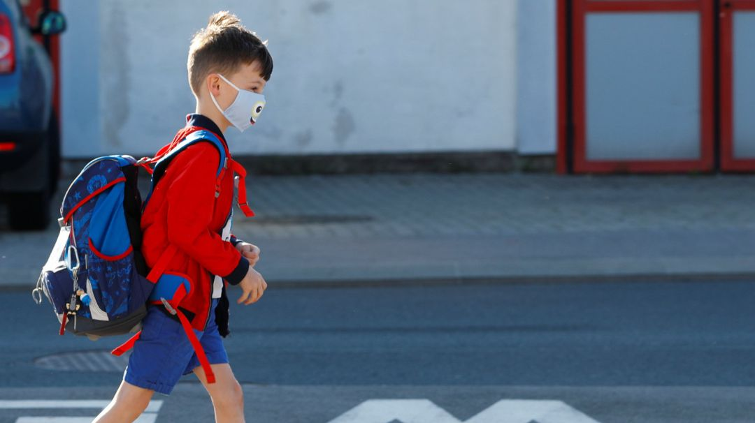 A child wearing a protective face mask walks a street as he arrives at a primary school