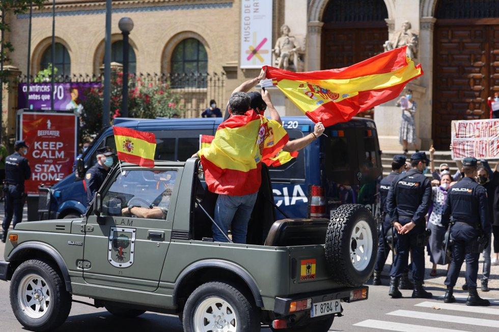 Coches y motos, con pancartas y banderas de España, circulan por las calles de Zaragoza en la manifestación de Vox para pedir la dimisión del Gobierno de Pedro Sánchez por su gestión durante la pandemia del COVID-19.