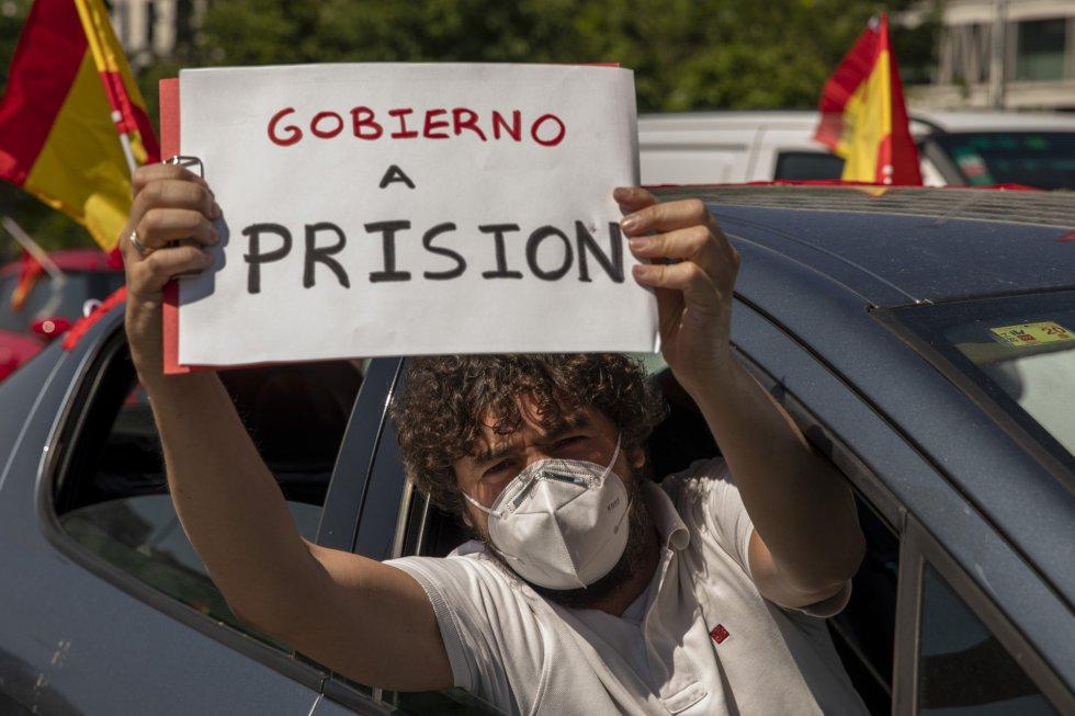 """Un hombre muestra el mensaje de """"Gobierno a prisión"""" desde su coche durante la manifestación de Vox contra Sánchez"""
