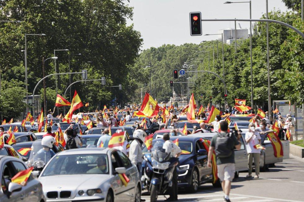 Coches y motos, con pancartas y banderas de España, circulan por las calles de la capital en la manifestación de Vox para pedir la dimisión del Gobierno de Pedro Sánchez por su gestión durante la pandemia del COVID-19.