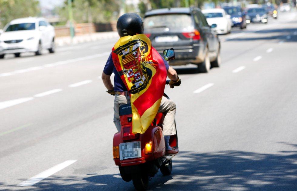 Un joven con una bandera pre-constitucional se adelanta a la caravana de coches convocada por Vox contra la gestión del Gobierno de Pedro Sánchez en la crisis del coronavirus.