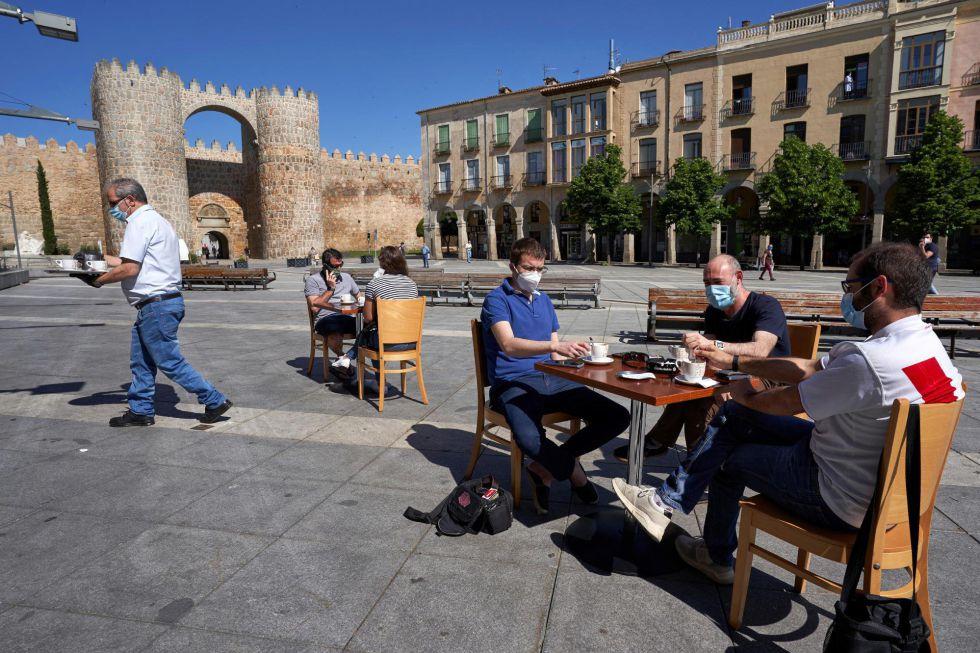 Varias personas desayunan en la terraza de un bar de la Plaza de Santa Teresa en Ávila este lunes, primera jornada de la fase 1 en la capital abulense.