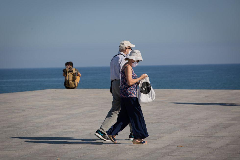 Dos personas protegidas con mascarillas pasean por el Paseo Marítimo de la Playa de la Barceloneta. Hasta el momento, en la ciudad condal tan solo estaba permitido el acceso a la playa entre las seis y las diez de la mañana.