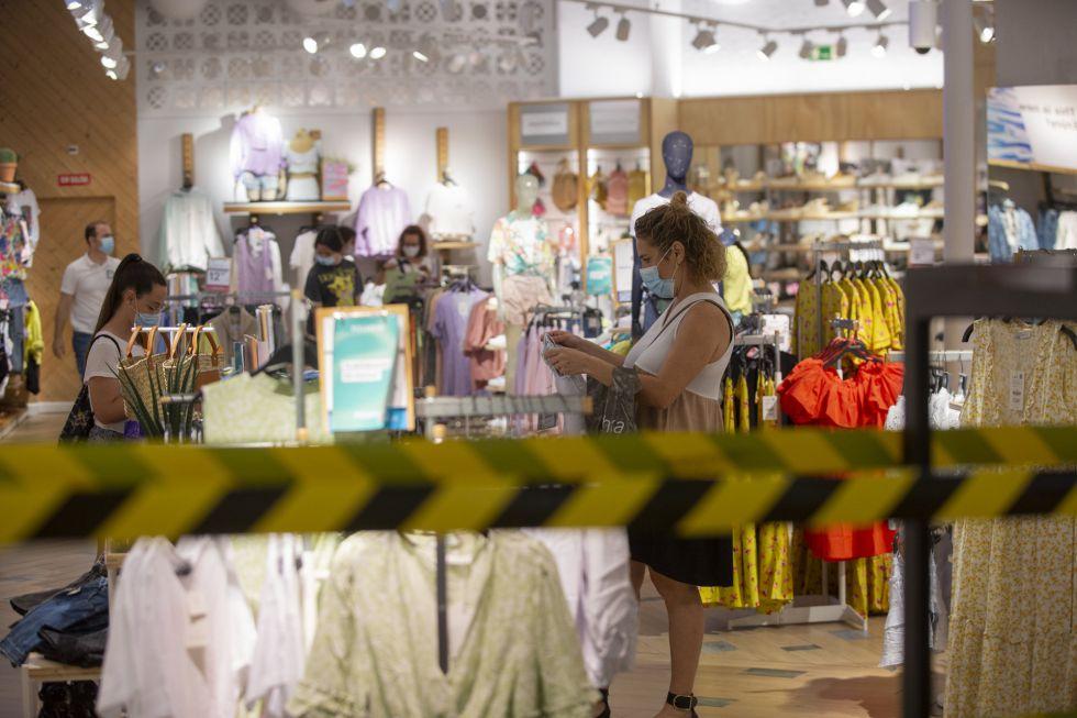 Algunas personas miran ropa en una tienda del centro comercial de Nervión durante el primer día de apertura de los centros comerciales al inicio de la Fase 2 del plan de desecalada en la capital andaluza.