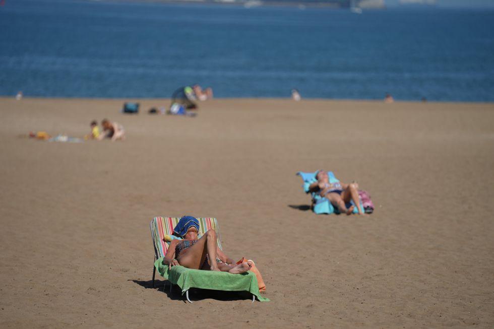 Varias personas toman el sol en la Playa de Ereaga, en Getxo, manteniendo distancias durante el primer día de la Fase 2, cuando se puede acceder a las playas .