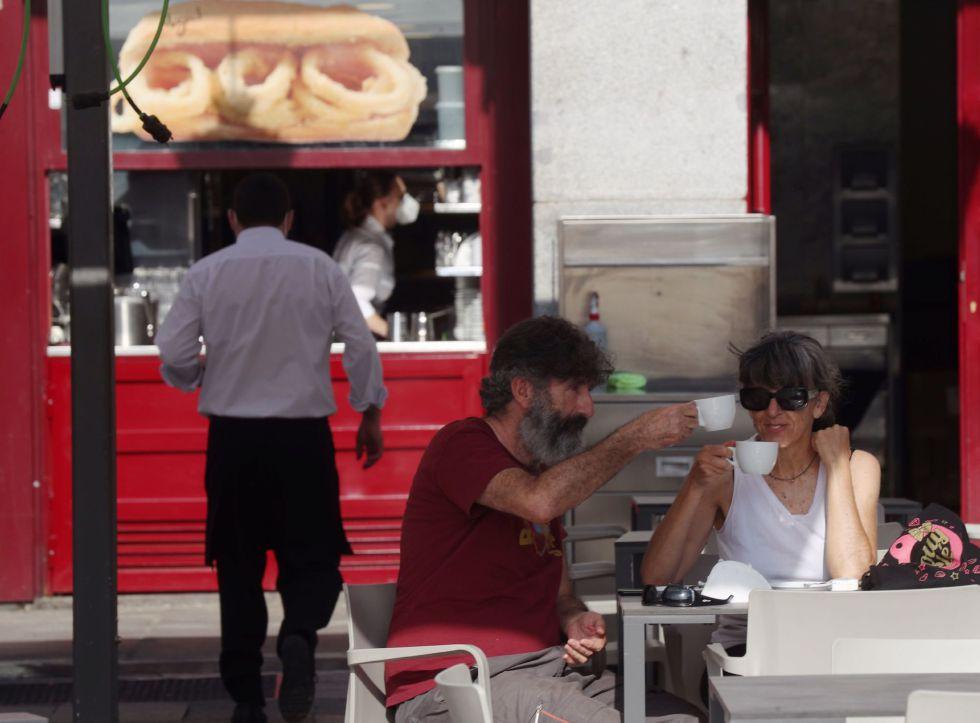 Dos personas disfrutan del desayuno en la terraza de un bar de la Plaza Mayor en Madrid este lunes.