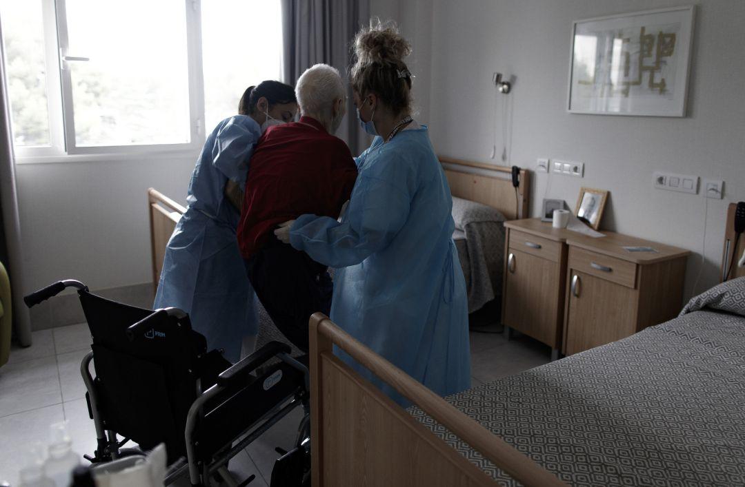 Sanitarias ayudan a un anciano en un centro de mayores.