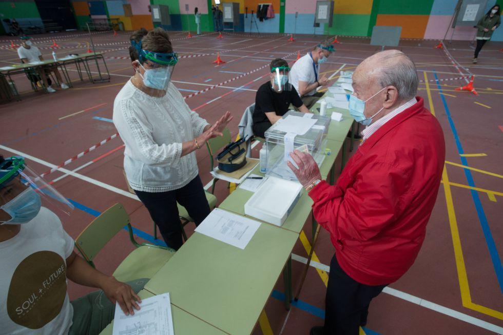 Un hombre muestra du DNI antes de depositar su voto en la urna manteniendo la distancia de seguridad con los miembros de la mesa electoral en un colegio de Burela (Lugo)