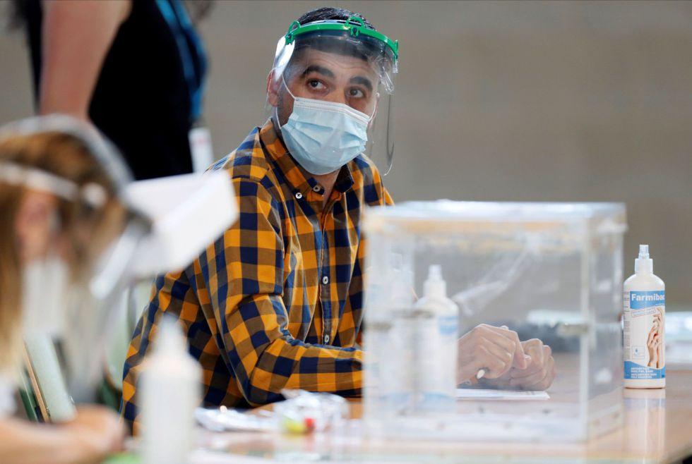 Un integrante de la mesa electoral de un colegio de Foz (Lugo) aguarda la llegada de votantes protegido con mascarilla y pantalla protectora.