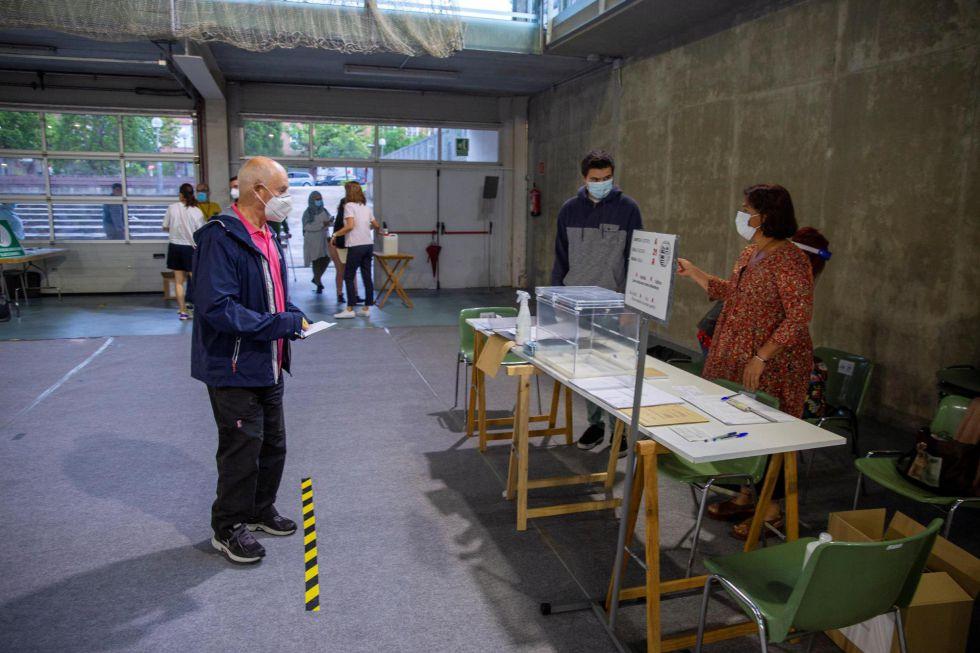 Respetando las marcas habilitadas en el suelo para cumplir la distancia social, los primeros votantes acceden de uno en uno a las urnas en puntos como Vitoria este domingo.
