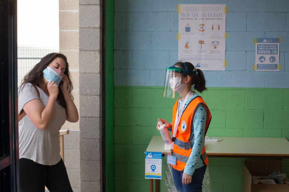 Una trabajadora de Protección Civil a las puertas de un colegio electoral en Galicia espera a que una votante se coloque su segunda mascarilla para ofrecerle gel hidroalcohólico antes de entrar.