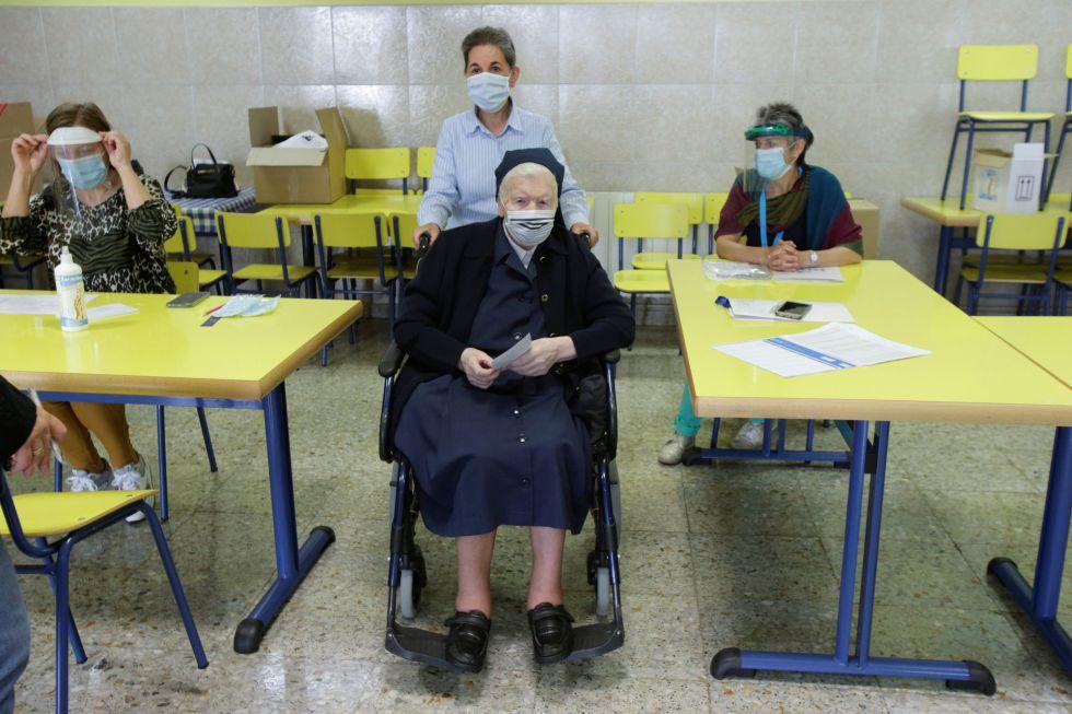 Una monja en silla de ruedas acude a votar a un colegio en Ribadeo (Galicia) con mascarilla y acompañada de otra mujer.