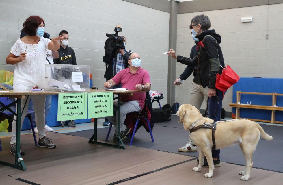 Una mujer invidente acompañada de su perro en el momento de votar en un colegio electoral en la localidad vizcaína de Durango, muestra su carnet de identidad guardando la distancia de seguridad.