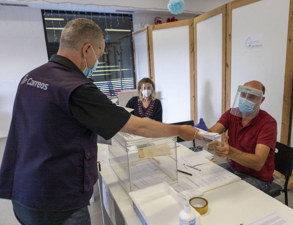 Un trabajador de Correos entrega los votos recibidos por correo en la mesa electoral de la ciudad de Laxe para las elecciones autonómicas al Parlamento gallego.