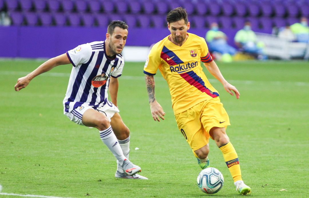 Lionel Messi of FC Barcelona and Kiko Olivas of Real Valladolid