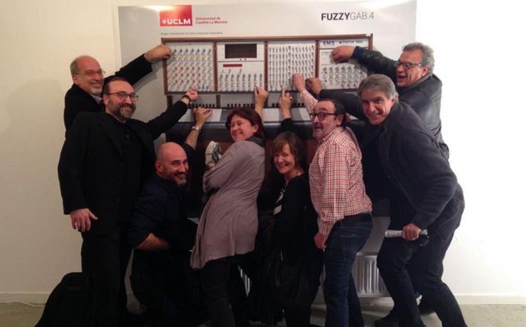 Profesionales del Grupo de Investigación Fuzzy Gab de la UCLM junto a una foto del Synthi 100.