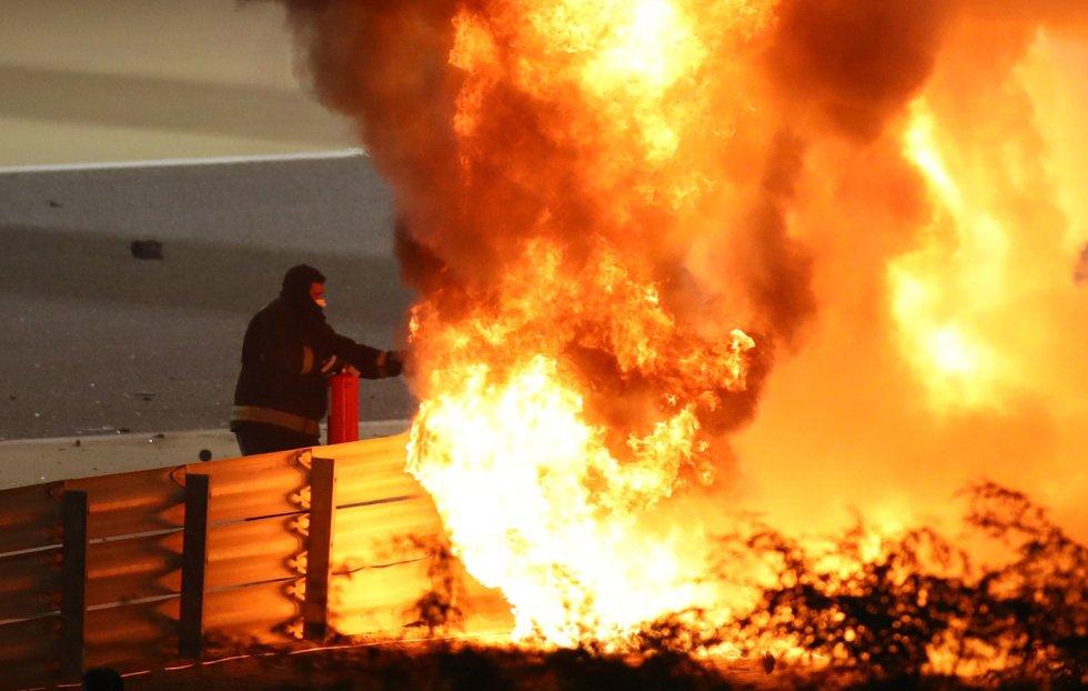 Intentan apagar las llamas en la escena del accidente después de que Romain Grosjean de Haas se estrellara al comienzo de la carrera