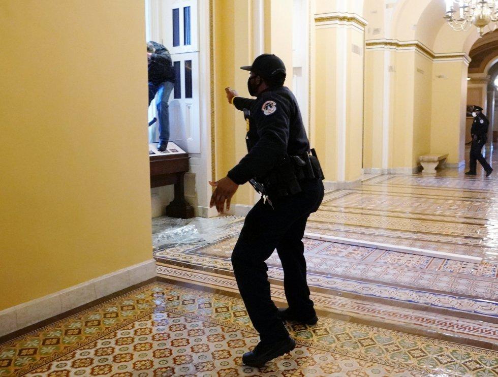 Un policía advierte a los seguidores de Trump para que no sigan avanzando en el interior del Capitolio.