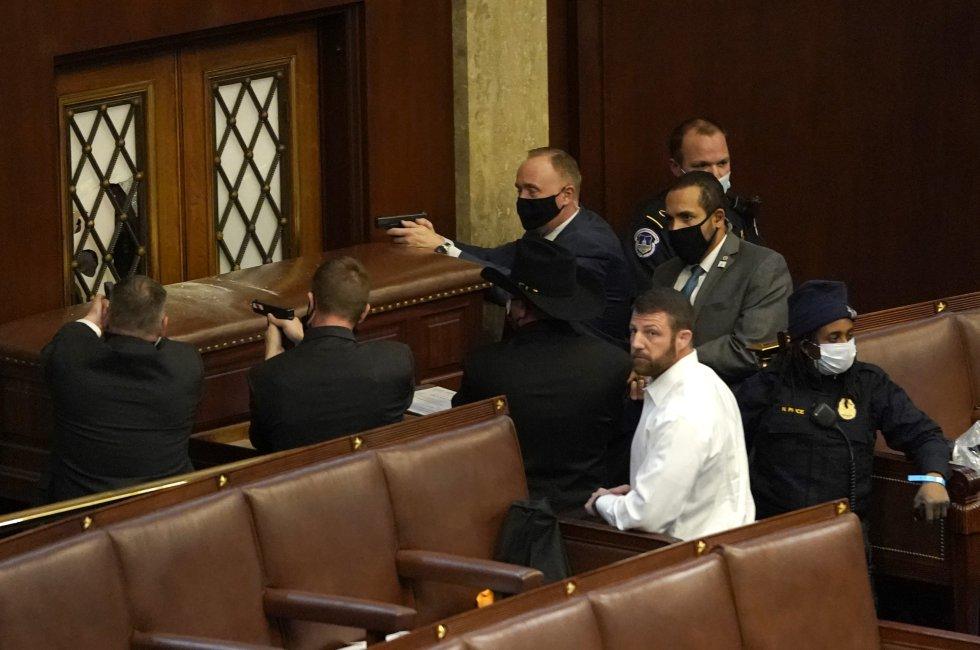Policías armados apuntan con sus armas a la puerta de la Cámara para evitar la entrada de los asaltantes.