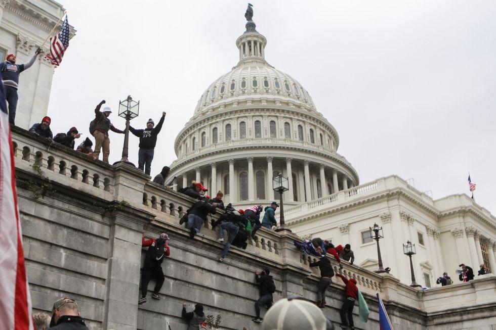 Defensores de Donald Trump trepan por los muros del Capitolio.