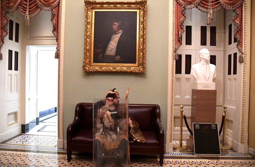 Un defensor de Trump sentado en un sillón de los pasillos del Capitolio.