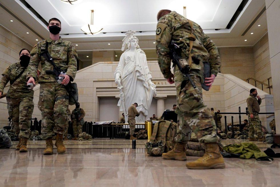Miembros de la Guardia Nacional se agrupan y descansan en el Centro de Visitantes del Capitolio antes del debate en la Cámara de Representantes sobre el impeachment de Donald Trump