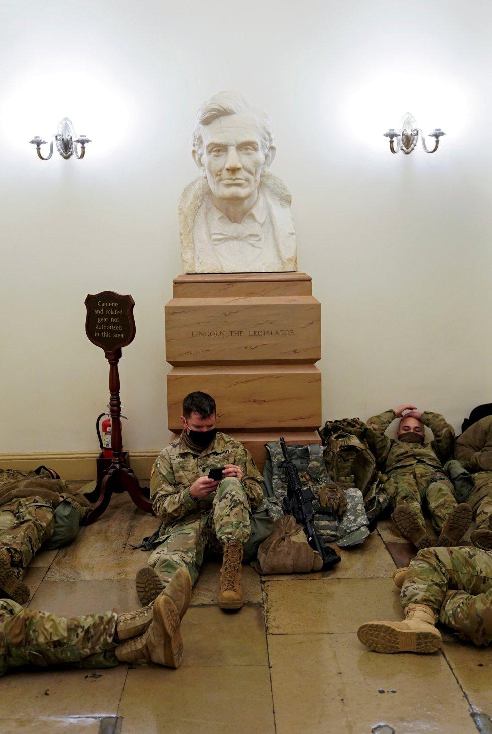 Los militares de la Guardia Nacional se agolpan en el interior del Capitolio y muchos de ellos tienen que descansar en el suelo junto a sus armas