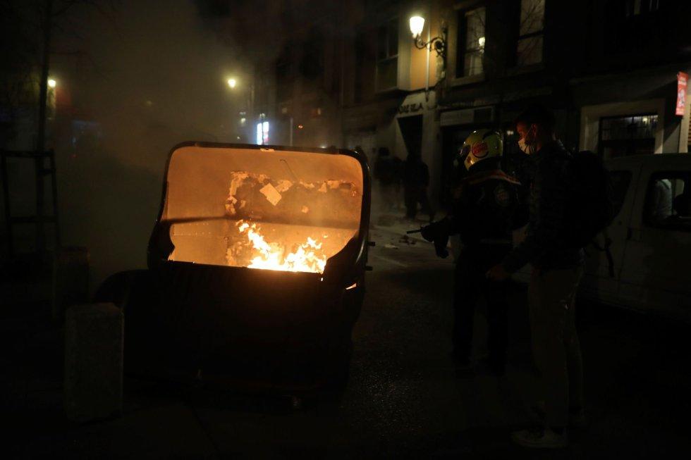 Un persona apaga un contenedor en llamas durante una marcha en Madrid por la detención del rapero Pablo Hasél