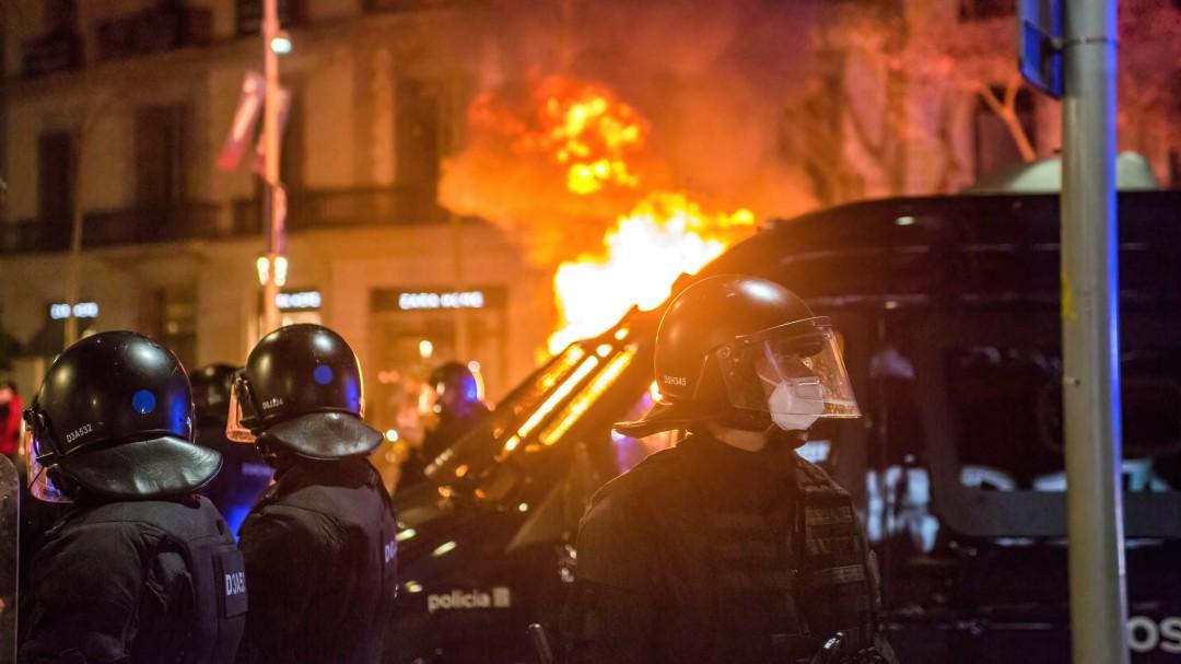 Manifestantes prenden fuego a un vehículo de la policía con agentes dentro en Barcelona y atacan cajeros